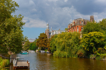 City view of Amsterdam canal, jetty and boat, Holland, Netherlan