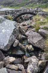 Old ancient packhorse bridge over mountain stream in Autumn