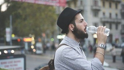 young hipster bearded man drinking in the city slow motion