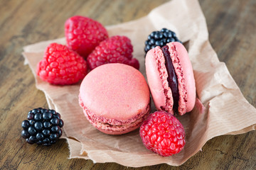 Macaroons and berry fruits on wooden background