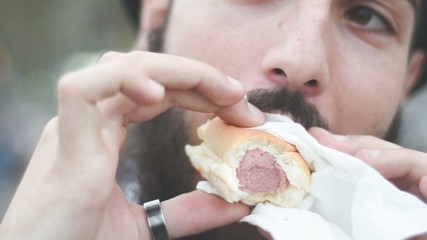 young hipster man eating hotdog in the city