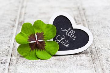 vierblättriges Kleeblatt mit Herz auf Holz, Alles Gute