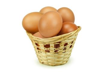 Куриные яйца в корзинке на изолированном белом фоне