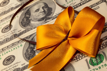 Packs of dollar bills with gold bow