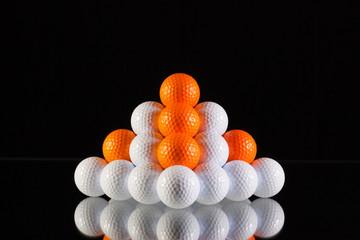 Pyramid of golf balls on a black background