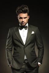 Handsome elegant business holding both hands in pockets.