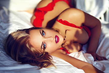 beautiful sexy blond model lying on white bed in lingerie