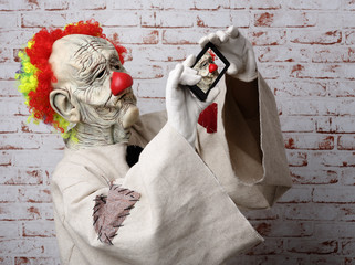 Sad clown makes selfie on cellphone.