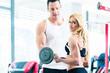 Frau im Fitness Studio übt mit Langhantel