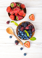 Вunch of wild berries and mint on a wooden board