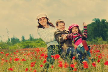 Vintage family on the poppy meadow