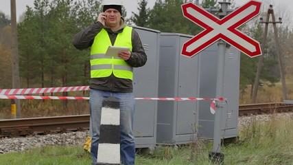 Railway engineer talking on cell phone before warning tape