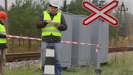 Railway engineer with tablet PC before warning tape