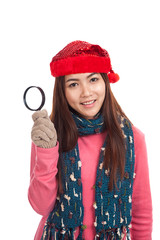 Asian girl with red christmas hat and magnifying glass