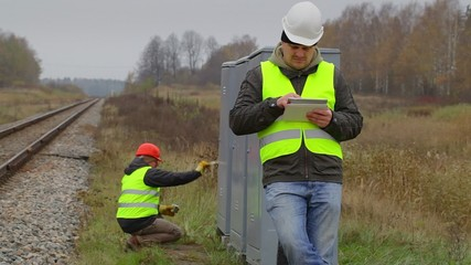 Railway engineer with tablet PC and worker in background