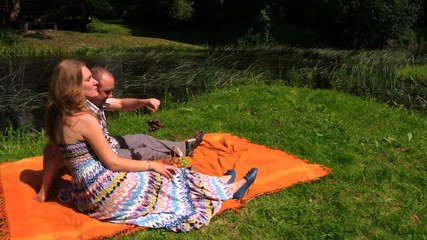 couple eat grape on plaid near stream. Picnic in summer day