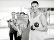 canvas print picture - group of smiling people with dumbbells in the gym