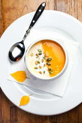 Pumpkin soup with cream and pumpkin seeds in a white bowl on woo