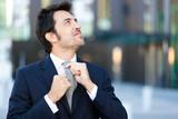 Confident businessman adjusting his tie