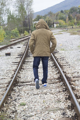 Man walking down the railroad with his hat on