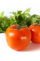 Red organic tomatoes in front of green lettuce