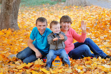 happy family, mother, father and son sitting on the autumn leave
