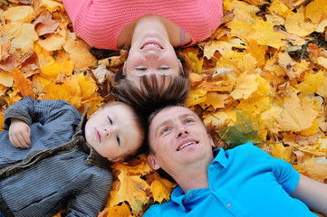 happy family, mother, father and son lying on the autumn leaves