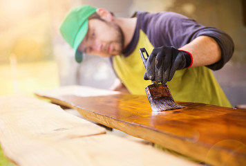Handyman varnishing wooden planks outside
