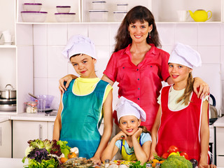 Mother and children cooking at kitchen.