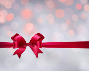 Red gift bow with ribbon on bokeh background.