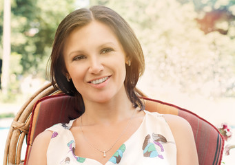 Smiling woman sitting in a garden chair