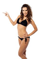 Smiling bikini woman pointing her finger
