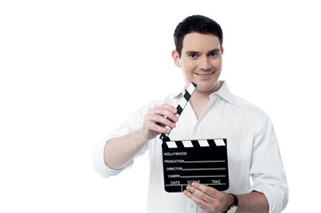 Smiling man holding a movie clap isolated on white