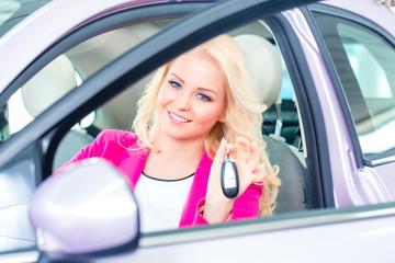 Frau kauft Auto im Autohaus