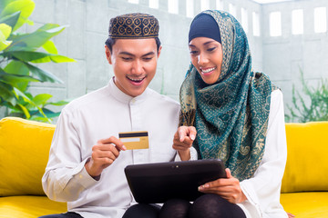 Asian Muslim couple shopping online on pad in living room