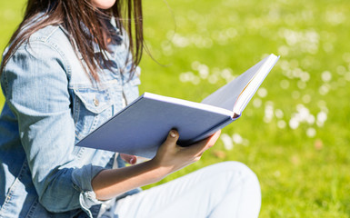 close up of smiling young girl with book in park