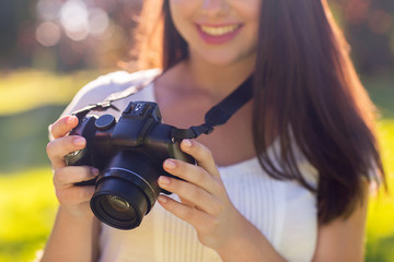 close up of young girl with photo camera outdoors