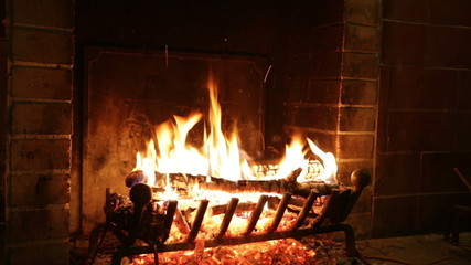 In an ancient stone fireplace fire burns