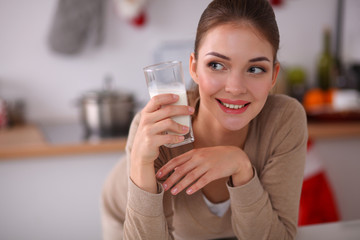Smiling young woman drinking milk, standing in the kitchen