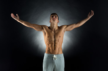 young male bodybuilder with raised hands