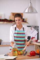 Smiling young woman  mixing fresh salad