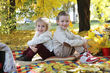 Sister and brother sitting back to back under autumn tree