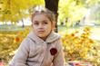 Girl looking up under autumn tree