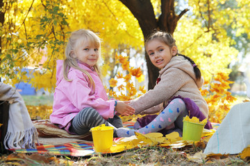 Happy girls playing under autumn leaves