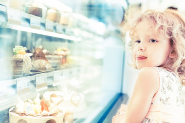 Young girl selection of cakes in the bakery section