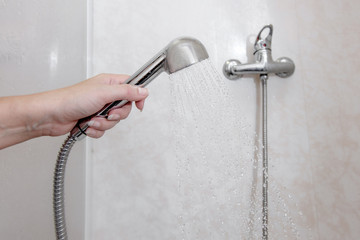 Womens hand holding shower head with pouring water in domestic