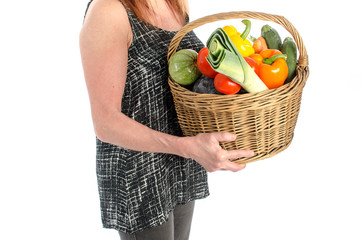 Woman holding a basket full of vegetables