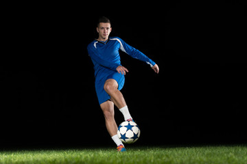 Professional Soccer Player Kicking Ball Isolated On Black