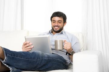 Hispanic man relax on couch using digital tablet or pad