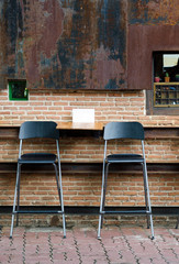 Two cafe chairs against brick wall